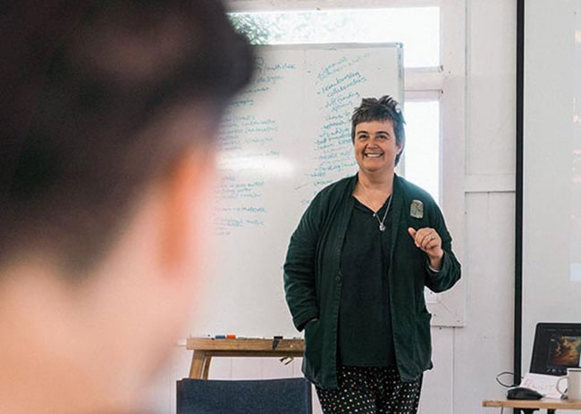 Felicity Letcher standing in front of a whiteboard presenting a workshop